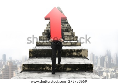 Businessman carrying big 3D red arrow sign and climbing on old concrete stairs with urban scene background - stock photo