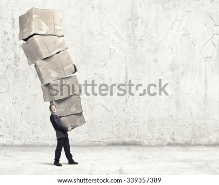 Businessman carrying big stack of carton boxes