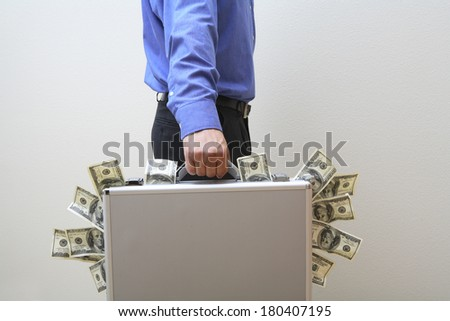 Businessman carrying briefcase overflowing with money - stock photo