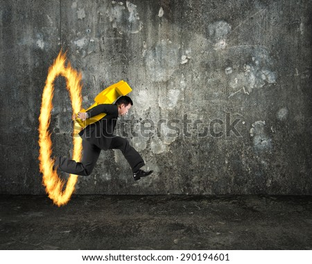 Businessman carrying 3D golden dollar sign, jumping through fire hoop, with dark concrete wall and floor indoors background. - stock photo
