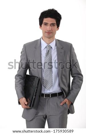 Businessman carrying laptop - stock photo