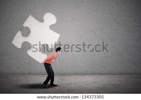 Businessman carrying puzzle on grey background