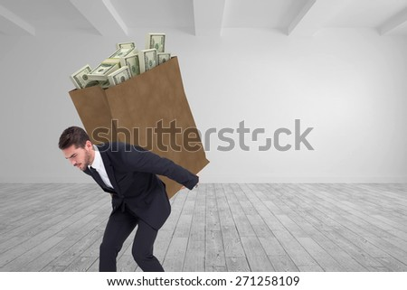 Businessman carrying something heavy with his back and hands against big room with white wall - stock photo