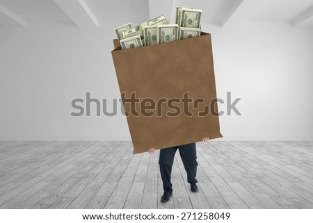 Businessman carrying something heavy with his hands against big room with white wall - stock photo