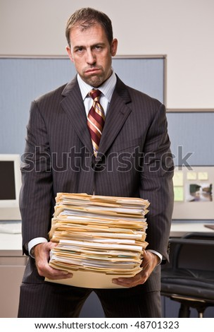 Businessman carrying stack of file folders - stock photo