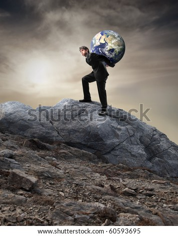 Businessman carrying the earth on his shoulders and climbing a rock - stock photo