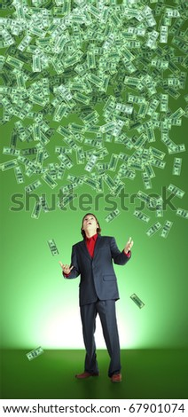businessman catchs flying banknotes on green background