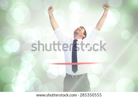 Businessman celebrating success with arms up against grey abstract light spot design - stock photo