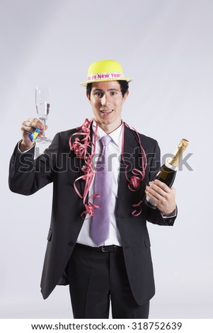 businessman celebrating the new year eve with champagne (isolated on gray) - stock photo