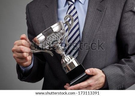 Businessman celebrating with trophy award for success in business or first place sporting championship win - stock photo