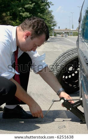 Businessman changing a flat tire on the road - stock photo