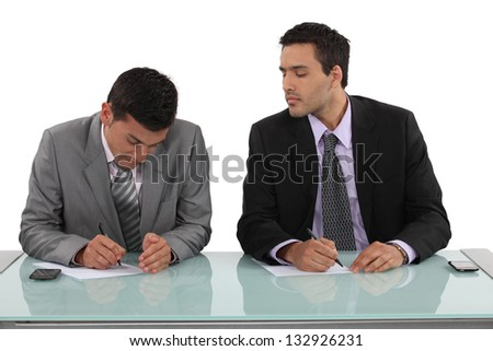 Businessman cheating in exam - stock photo