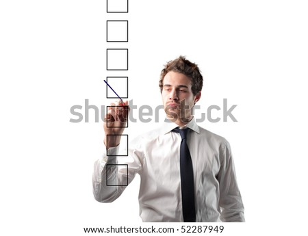Businessman checking a box with his pen - stock photo