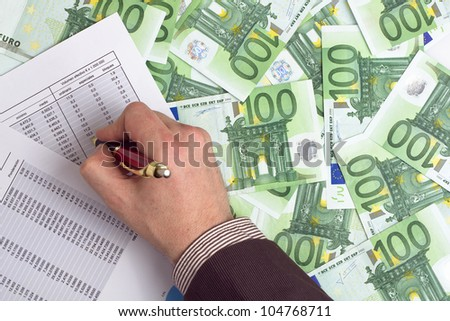 Businessman checking earnings on background of banknotes - stock photo
