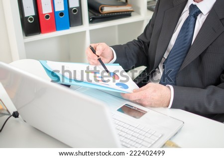 Businessman checking financial graphs at the office - stock photo