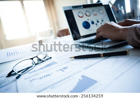 Businessman checking reported profits on the paper and laptop. - stock photo