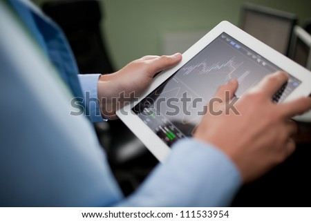 Businessman checking stock market on tablet