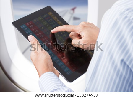 Businessman checking stock market on tablet in airplane - stock photo