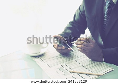 businessman checking stock with mobile phone coffee and newspaper on the desk vintage style color tone  - stock photo