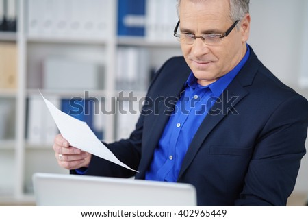Businessman checking the information in a document on a laptop computer as he works at his desk in the office, close upview