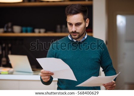 Businessman checking the paperwork at home.