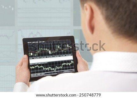 Businessman checking the stock market on digital tablet in office - stock photo