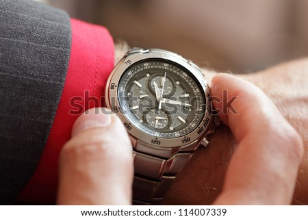 Businessman checking the time on his wrist watch - stock photo