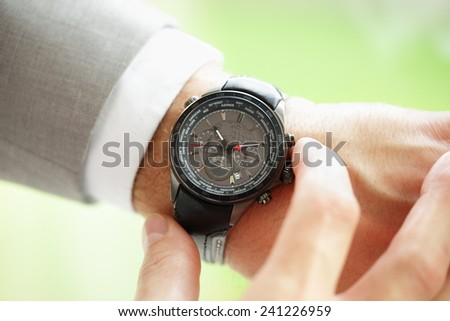 Businessman checking the time on his wrist watch concept for urgency, deadline or running late - stock photo