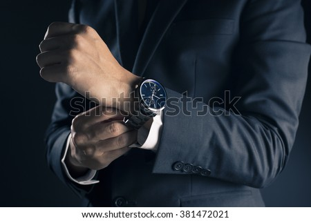 Businessman checking time from watch - stock photo