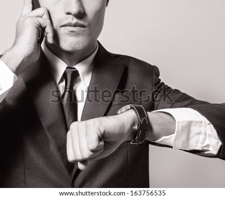 Businessman checking time on his watch while in on the mobile phone - stock photo