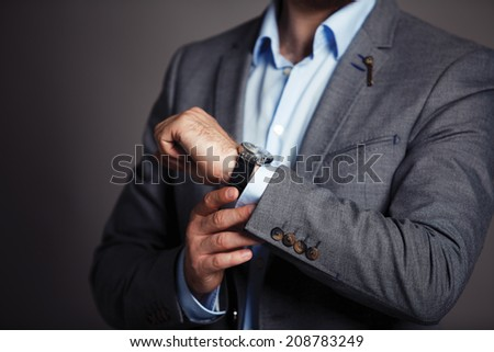 Businessman checking time on his wristwatch. men's hand with a watch.  - stock photo