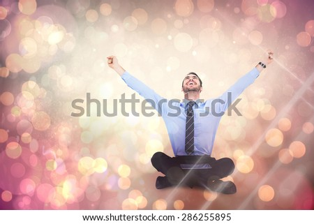 Businessman cheering with tablet sitting on floor against yellow abstract light spot design - stock photo