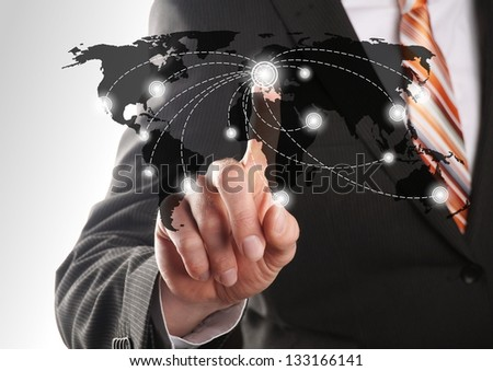 businessman choose one of his global network of a worldmap - stock photo