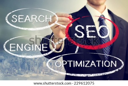 Businessman circling SEO bubble over big city background - stock photo