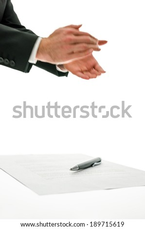 Businessman clapping his hands applauding a colleague, at an event or speech or for a successful business venture with a pen and paperwork below, isolated on white. - stock photo
