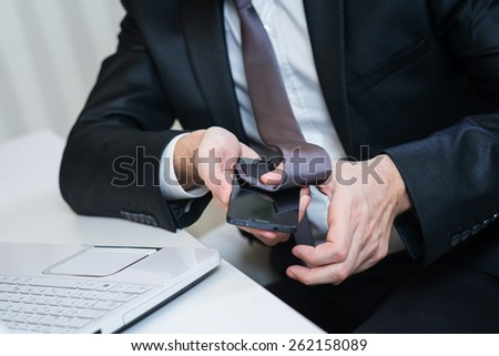 Businessman cleaning his smart phone with tie. Display cleaning. - stock photo