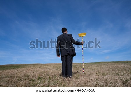 businessman cleaning the field with a broom - stock photo