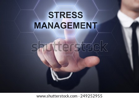 businessman clicks on virtual touchscreen display and select stress management - stock photo