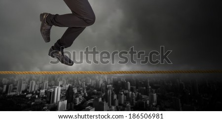 businessman climb rope be danger with storm - stock photo