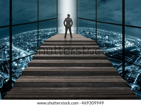 Businessman climbed on top of the stairs which can see top view of cityscape over the clouds background ,Success business and Ambitions concept
