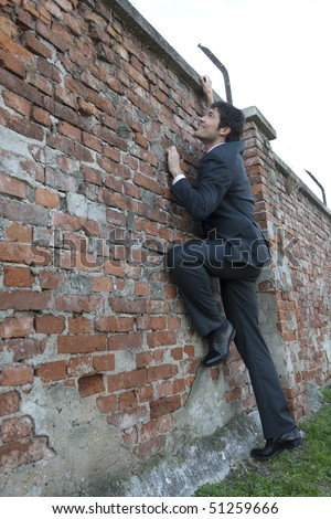 Businessman climbing a brick wall. Concept: climbing to success