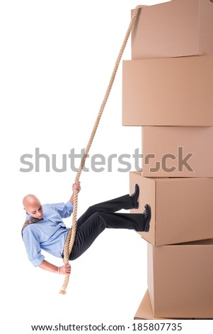 Businessman  climbing a cardboard box cliff with a rope - stock photo