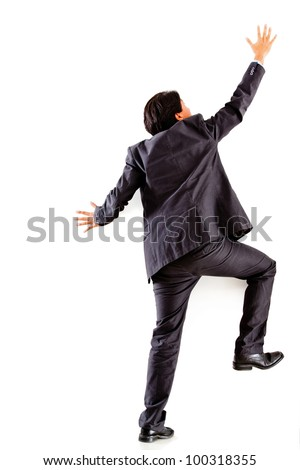 Businessman climbing a wall - isolated over a white background