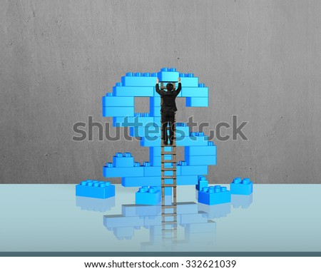 Businessman climbing ladder and holding a blue block to complete dollar sign shape of stack blocks, with concrete wall background. - stock photo