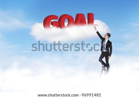 Businessman climbing ladder to set his goal high - stock photo