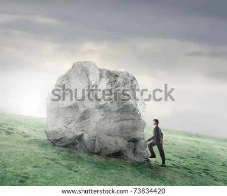 Businessman climbing on a rock on a green meadow - stock photo