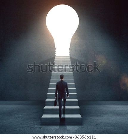 businessman climbing on concrete ledder to  open door in form lamp - stock photo