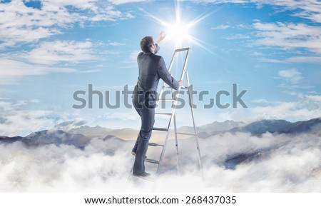 Businessman climbing on ladder in the clouds - stock photo