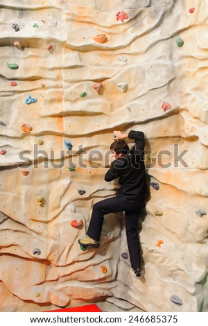 Businessman climbing on man-made cliff in the sport centre - stock photo