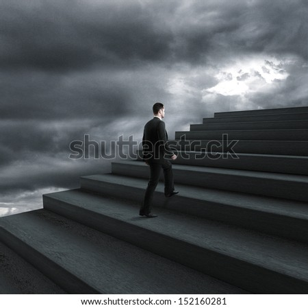 businessman climbing stairs in bad weather - stock photo